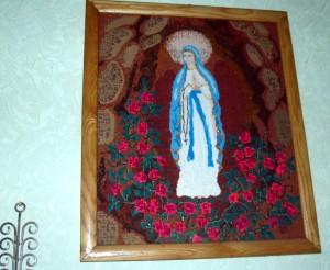 Išsiuvinėtas šv. Mergelės Marijos paveikslas puošia miegamojo sieną.   Autorės nuotr.